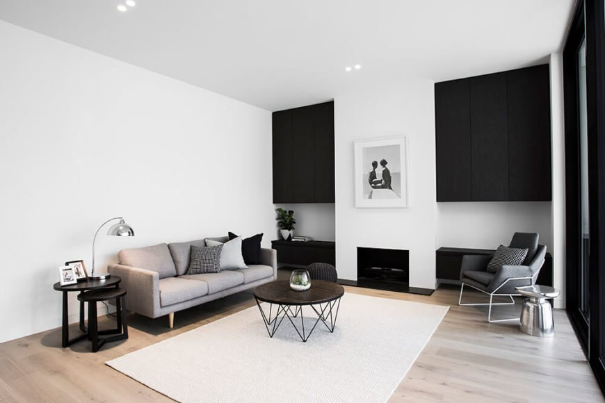 The smaller relaxing space enjoys a secondary fireplace, flanked by black painted wood cabinetry. The subtle color palette makes for a truly cohesive sense of style.