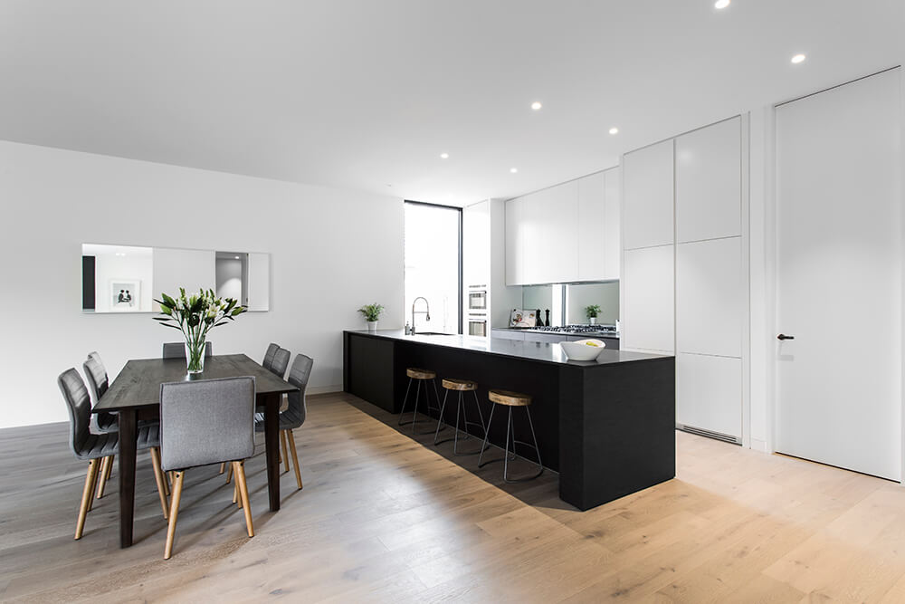 Large galley kitchen with white walls and ceiling, paired with black center island and dining table set.