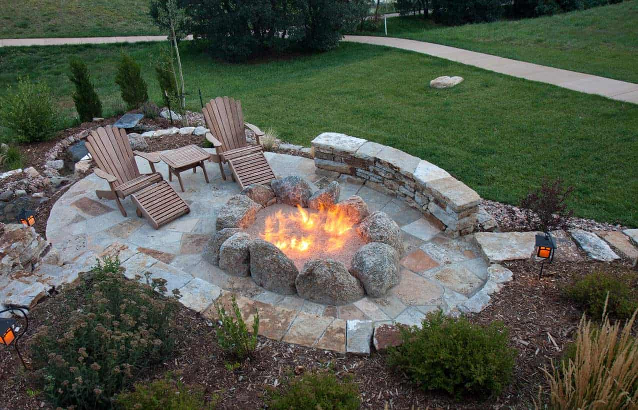 Large fire pit on patio built with huge boulders.