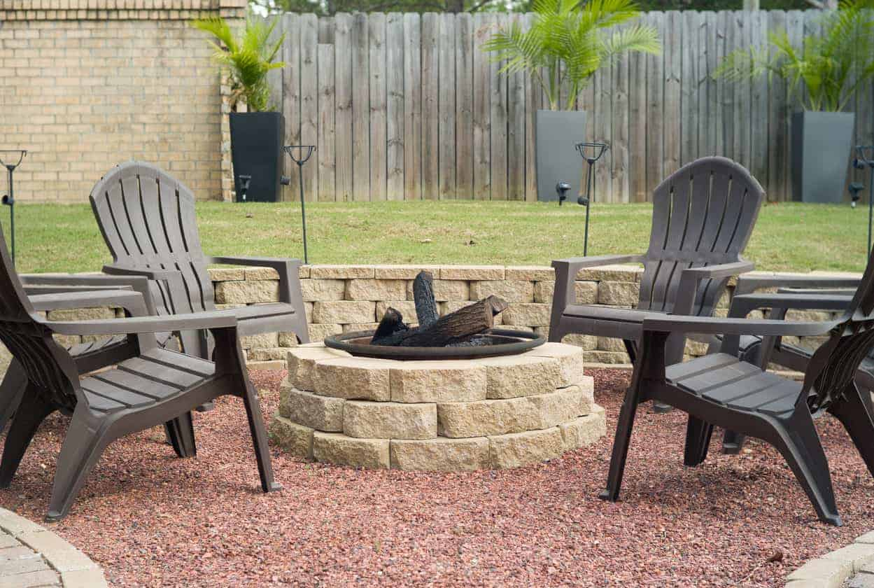 Above ground cobblestone fire pit in sunken patio area surrounded by comfortable plastic Adirondack chairs.