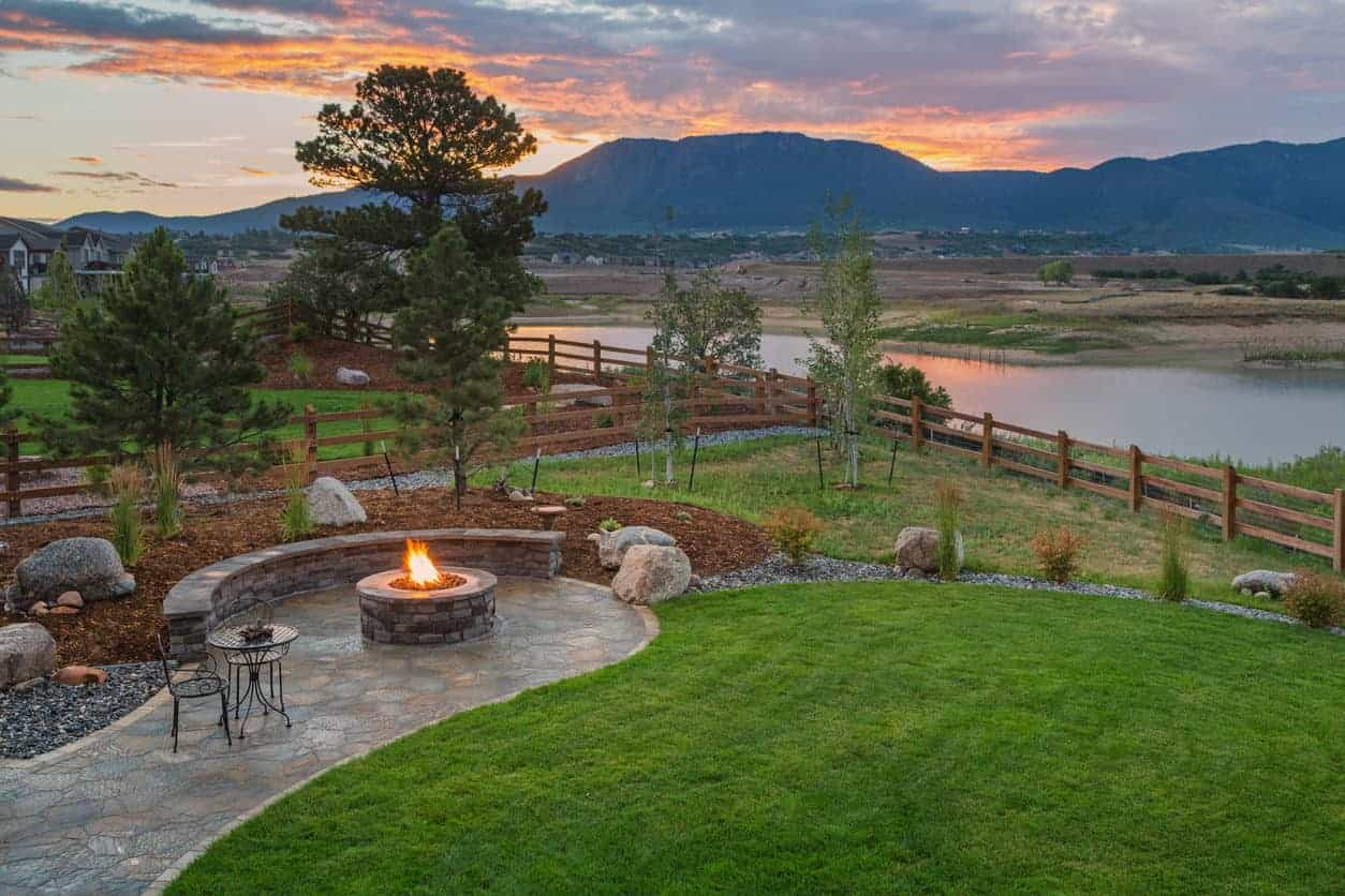 Bucolic backyard with flagstone patio next to elevated garden with round fire pit overlooking a body of water.