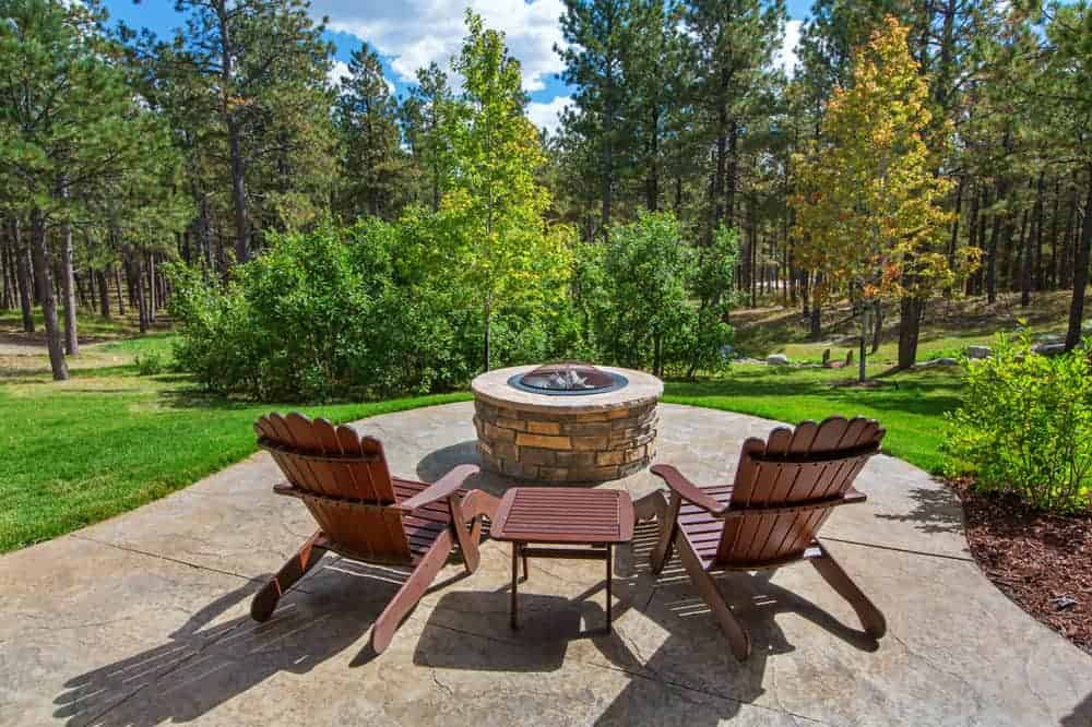 Fire pit alcove on patio with incredible view of a forest below.