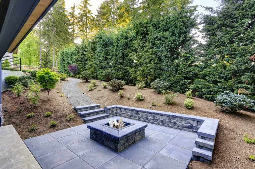 Custom-built square wood-burning fire pit on square patio.