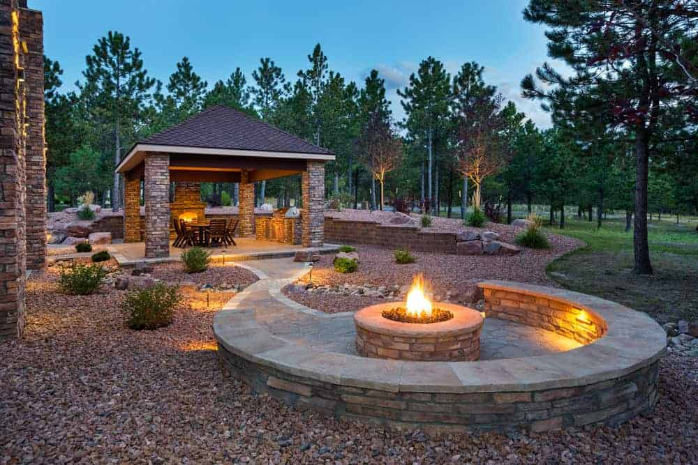 Spectacular custom built fire pit area with built-in bench off a pavilion-covered patio in large backyard.