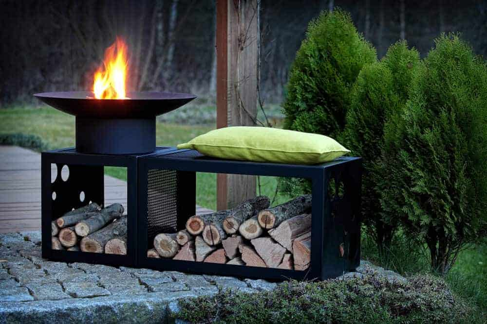 Black metal round fire pit with wood storage and bench.