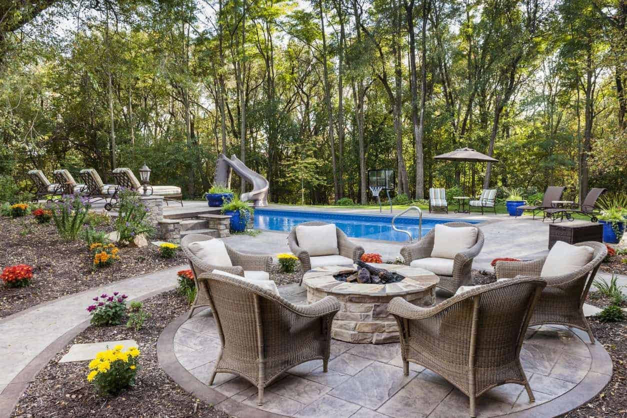 Stone above-ground round fire pit on patio next to a backyard swimming pool.