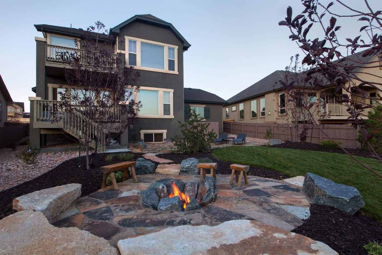 Rustic large boulder in-ground fire pit on patio in the middle of the backyard.