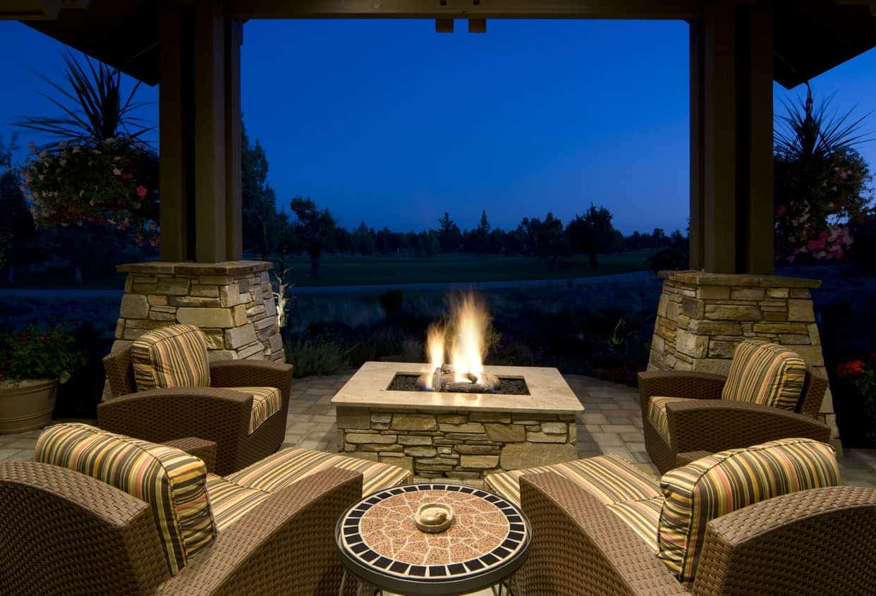 Square stone fire pit and table on covered patio surrounded by large overstuffed patio armchairs.