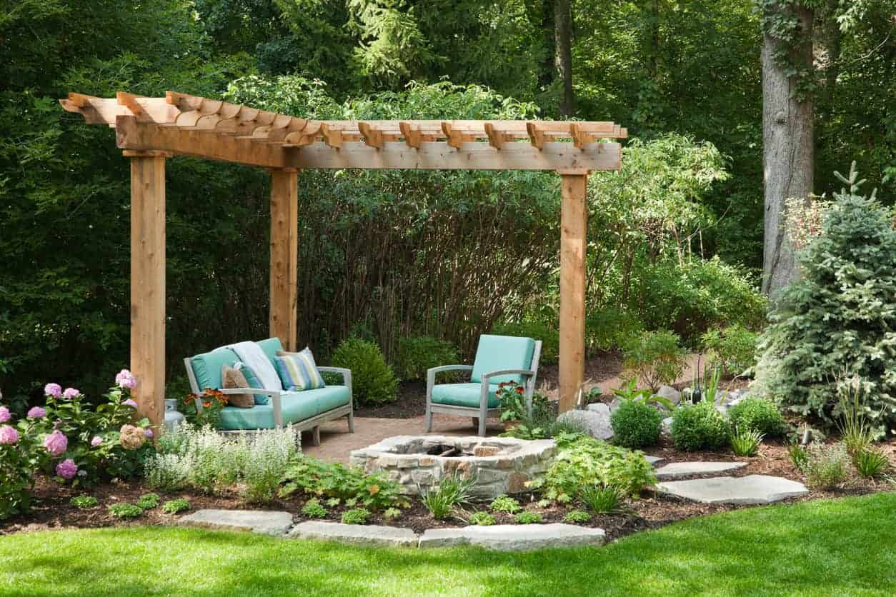 Small patio under trellis in the garden with a small fire pit.