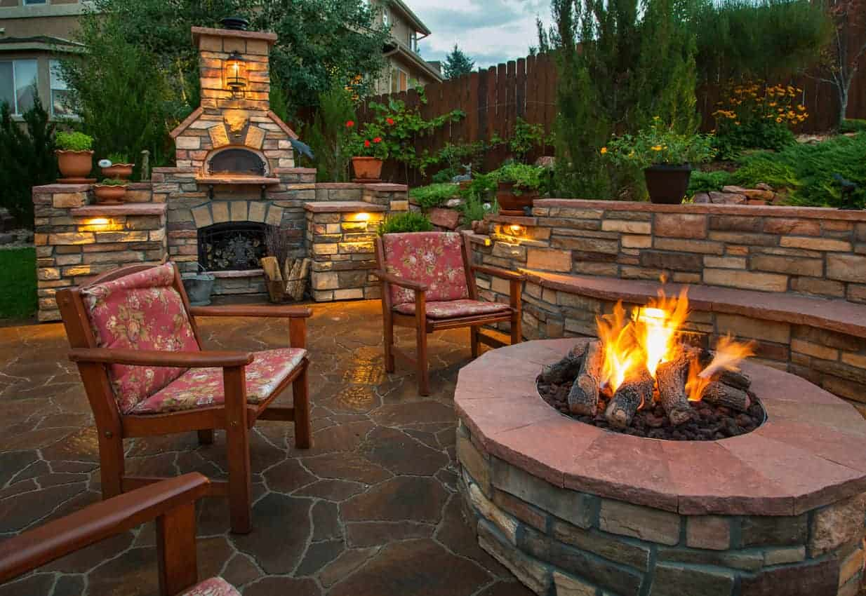 round red brick fire pit on flagstone patio in stunning backyard. The patio includes wood-burning fireplace as well.