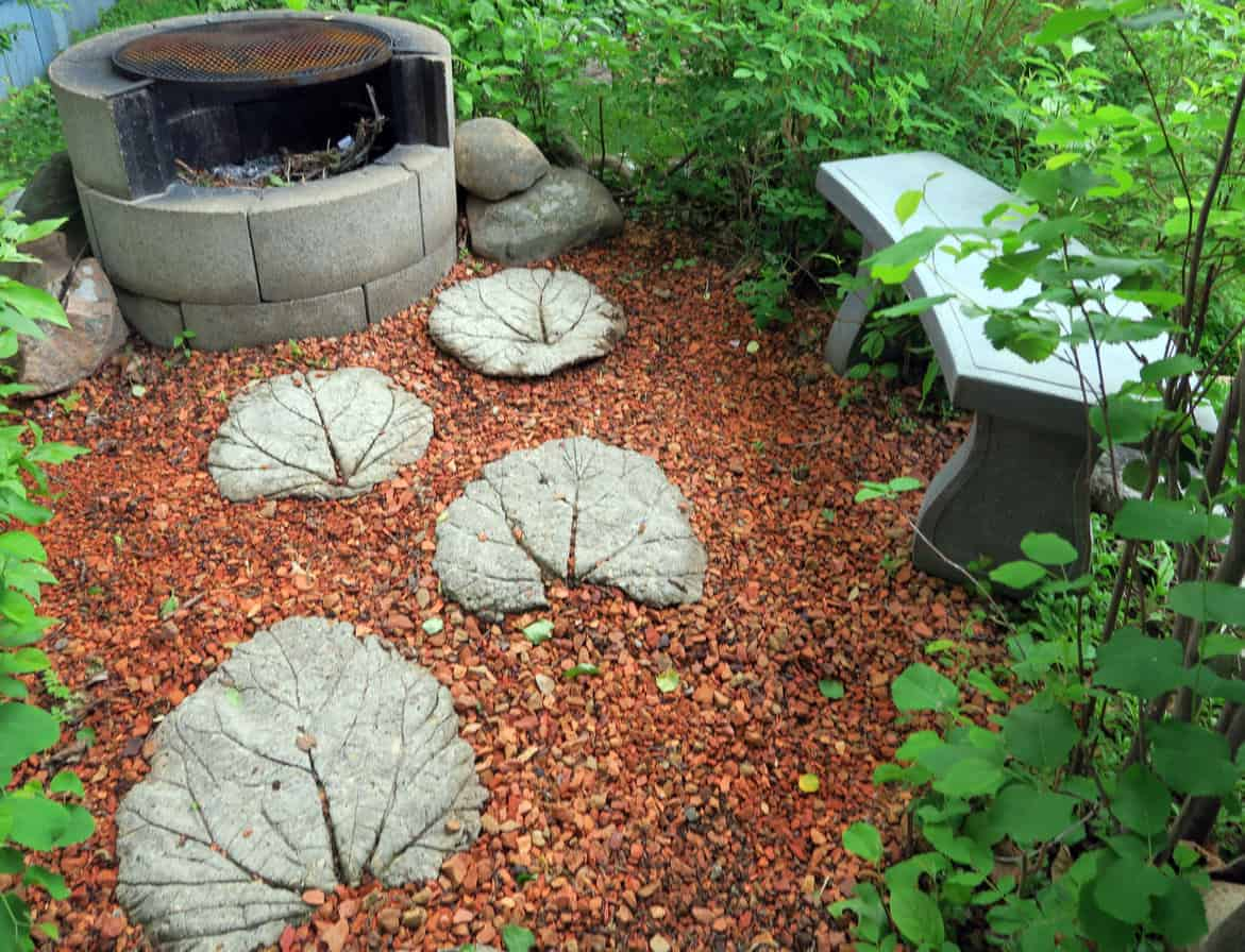 Round cinder block fire pit with grill cover in small garden patio area.