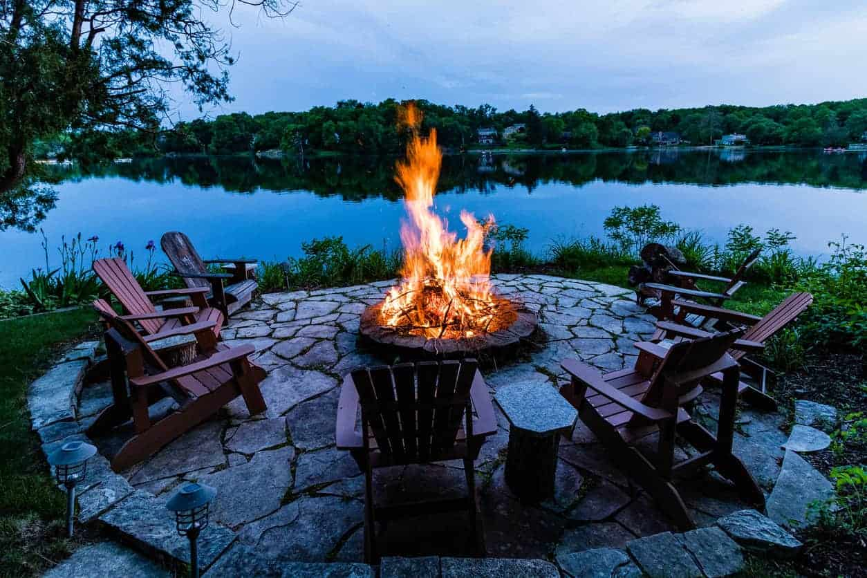Lakeside round fire pit on round flagstone patio overlooking calm lake.