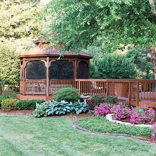 This deck side gazebo sits amongst a lovely garden. The screens keep out the insects that have come to check out the flowers, but do not hinder the view of the pretty plants and trees.