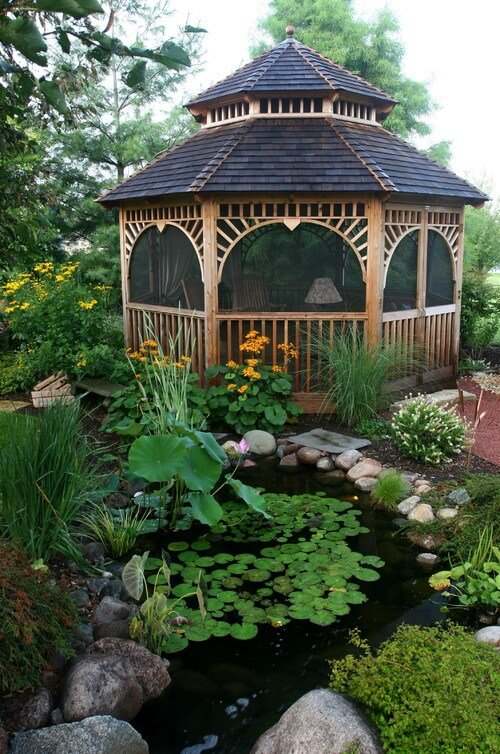 This wooden gazebo sits next to a large pond water feature. It is also screened in which protects occupants from any insects that may come from having a water feature like this.