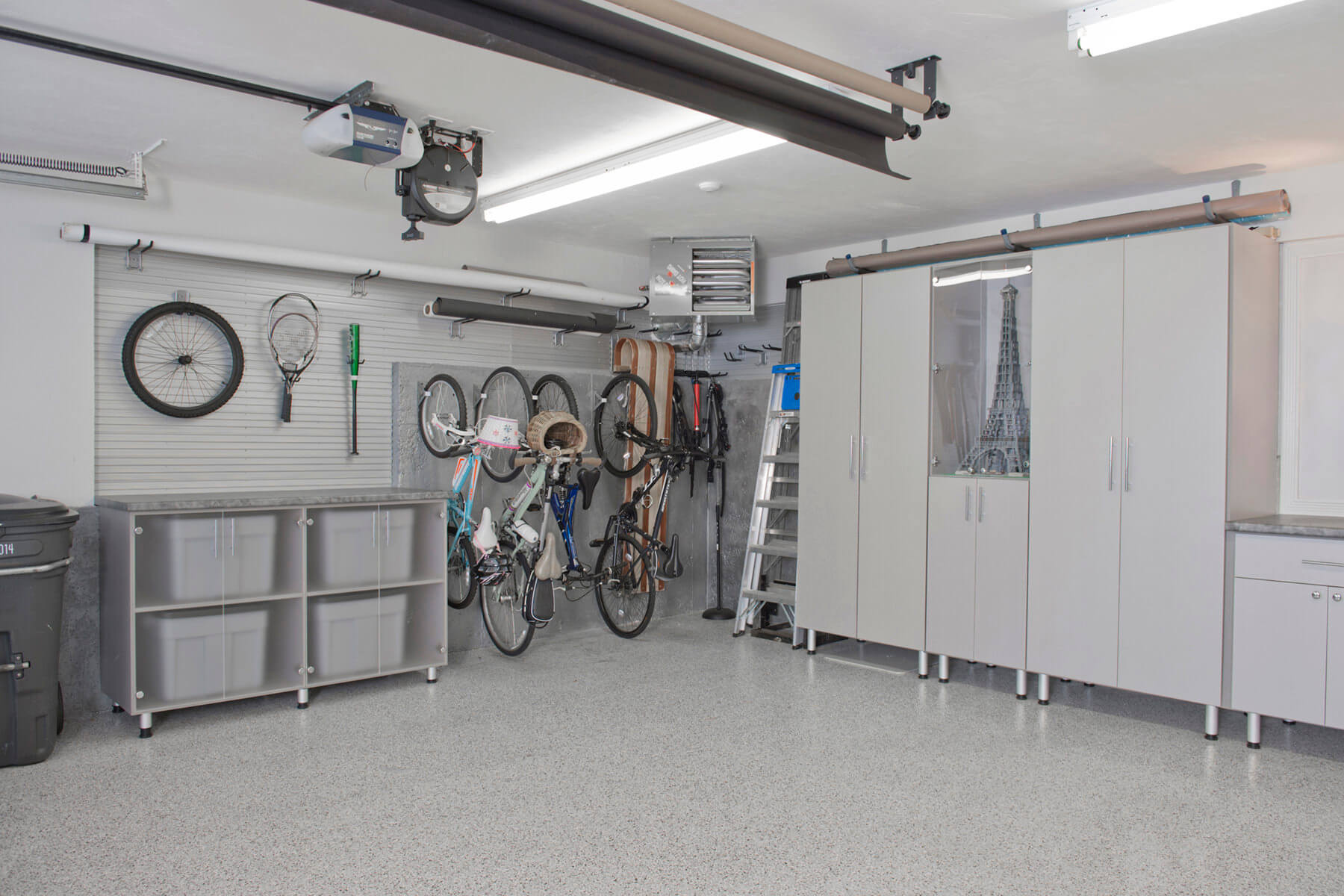 An example of a well-organzed garage using a slatwall, vertical bicycle storage and garage cabinets. All storage implements are in off white to match garage interior. Garage floor is a polyaspartic flooring (see section C below).