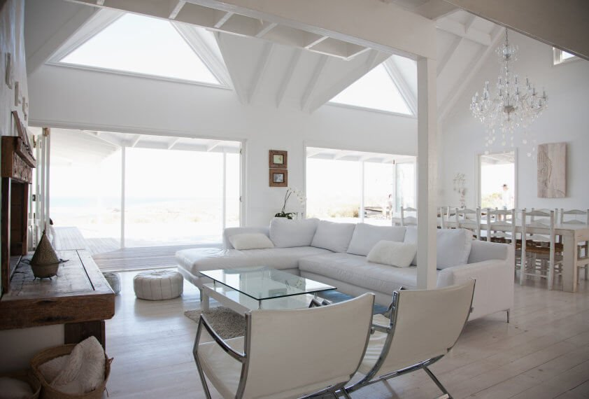 Large living area featuring white walls and a white tall ceiling. It also offers a white L-shaped sofa and a glass top center table.