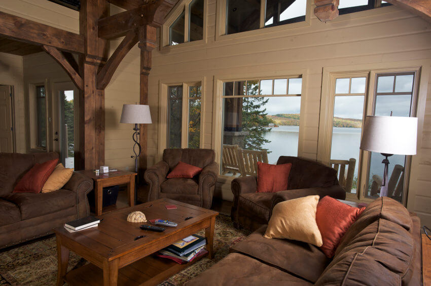 This living room features brown seats and cream walls. The home features a tall ceiling with exposed beams as well.