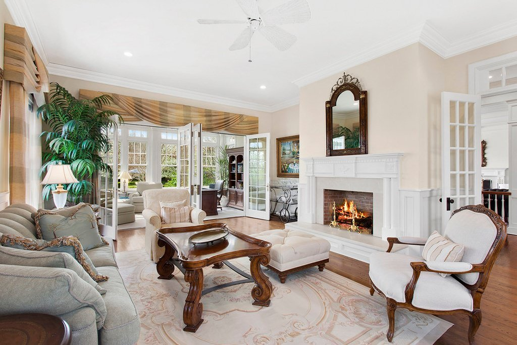A traditional interior with heavy wood carving on the center table and chairs. Extra soft pillows and sumptuous sofa rest on a walnut floor covered with a faded carpet.