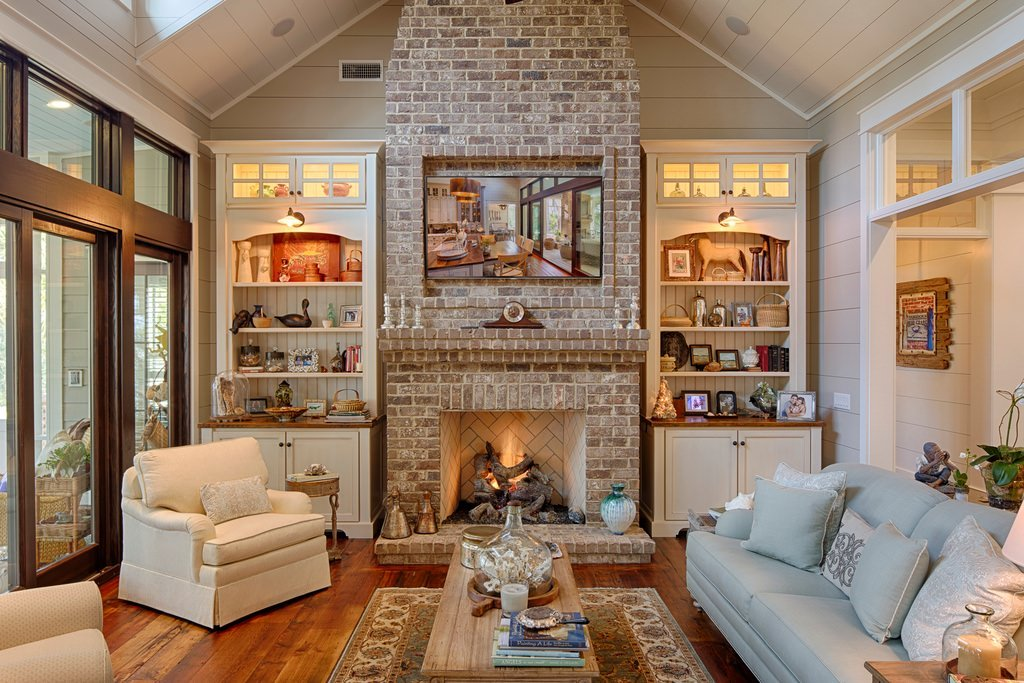 The simplicity of this country inspired living room is accented with a few picture frames, animal and human figures sitting throughout white painted shelves. It represents the normal lifestyle of the homeowner.