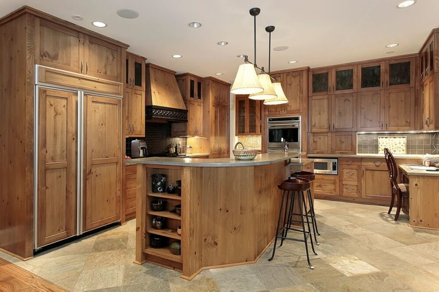 This kitchen has a bit of a vintage feel to it, especially with the faux panels covering the refrigerator. The focus here is on the natural wood of the cabinetry, along with the textured stone flooring.
