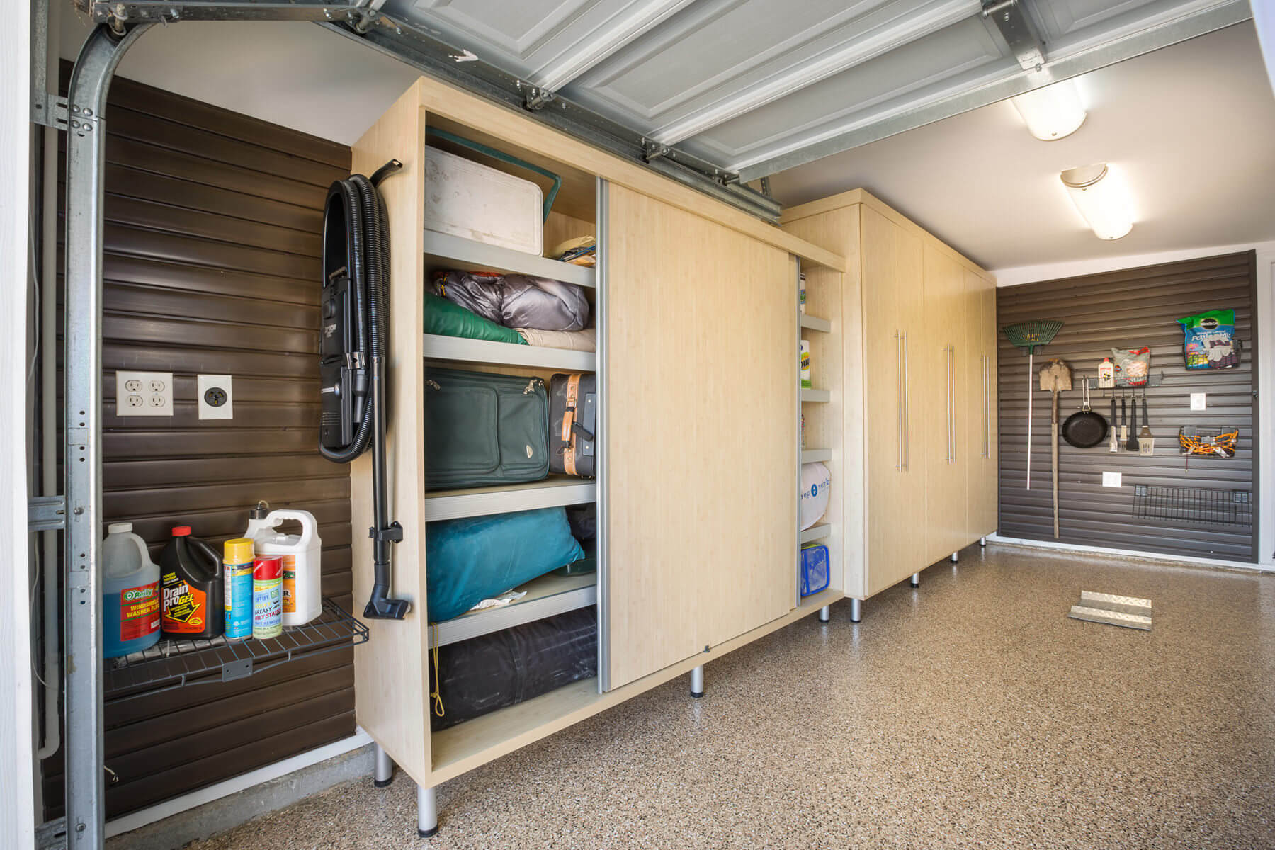 On another side of the garage is a large-sized rectangular maple melamine cabinet with full sliding doors allowing for easy access to belongings whenever the car is parked inside.