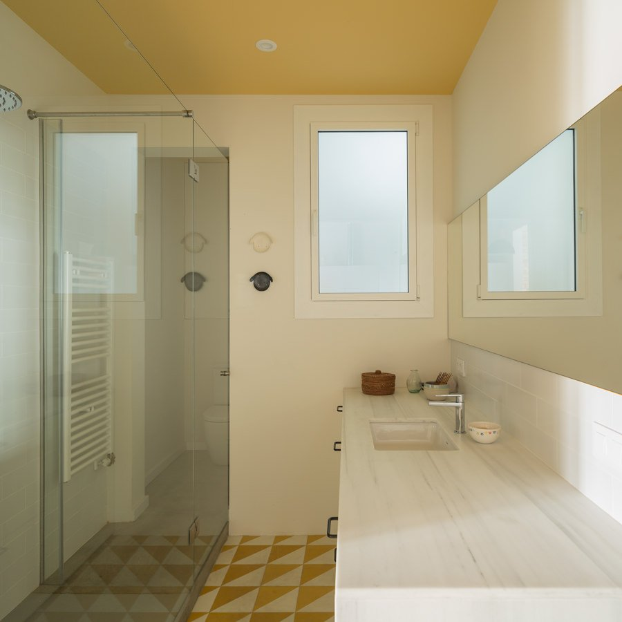 A conventional bathroom turned into a transitional and functionally styled one, with a working fixture and sink plus the sliding glass panel that saves space.
