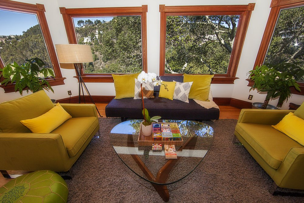 The richness of the cool greenery stands out while the hard wood floor and window frames highlights the space with yellow accents contrasting the tone.
