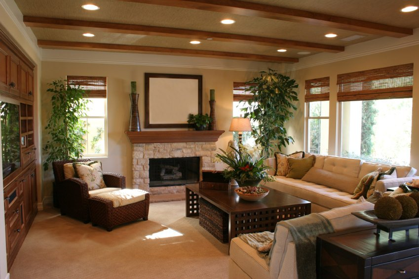 Hardwood furniture is present along with exposed beams in the ceiling. It also has a wood and stone fireplace.