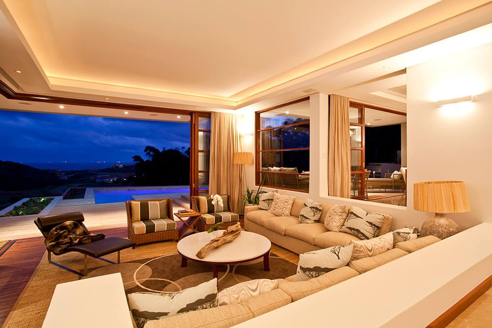 A large formal living space with a nice set of seats under the luxurious tray ceiling.
