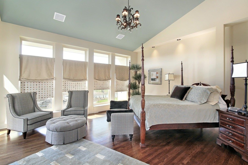 Grey fabric covered arm chairs bring a simple and modern look to this bedroom highlighted by a four-post bed.