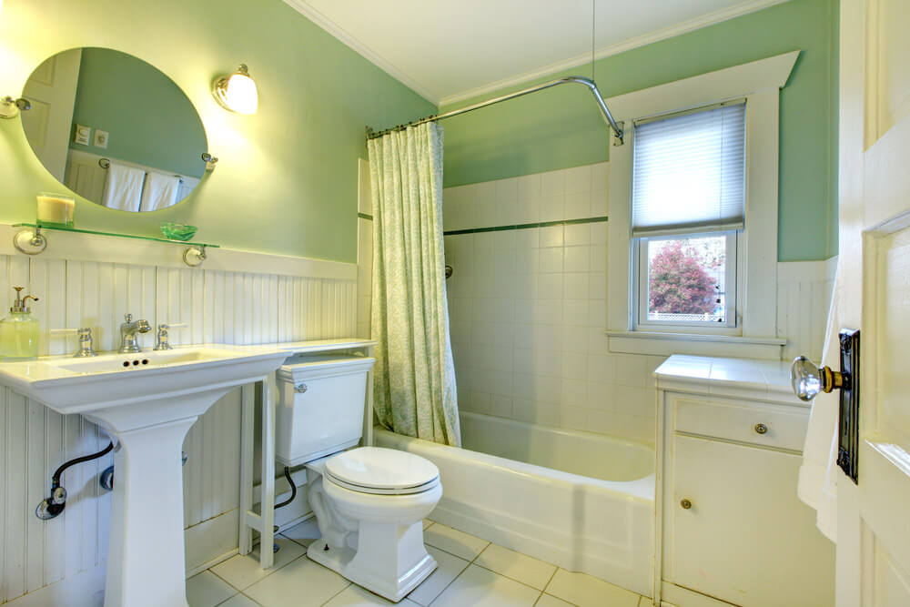 The light green and white wall and vanities combine to create a cool color combination that creates a relaxing and refreshing mood.