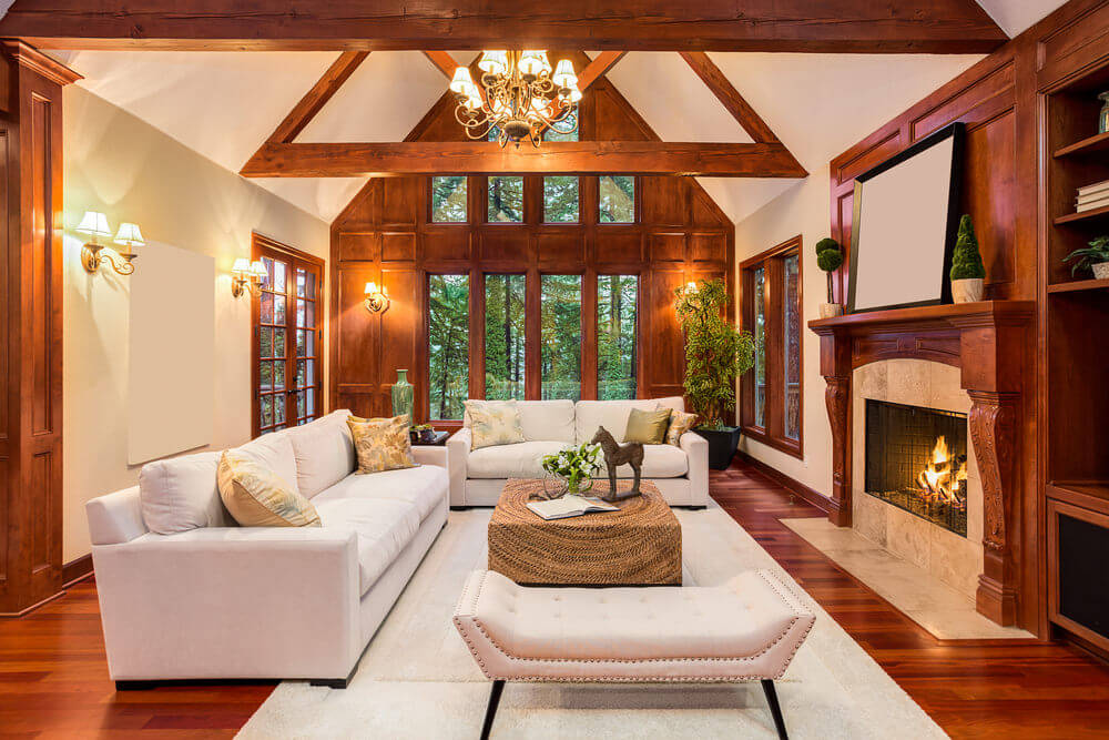 Large living room featuring a strong wood tone all over the place. The room offers comfy seats and a large fireplace.