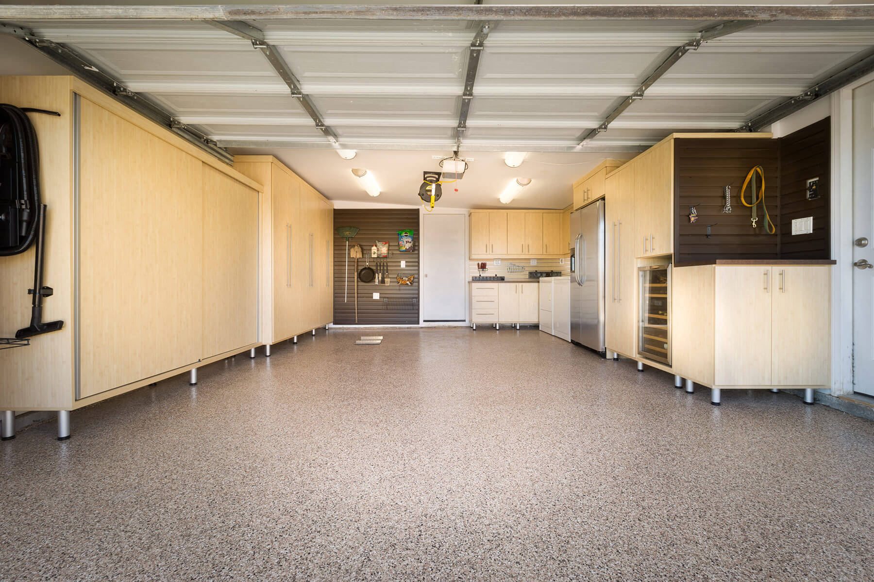 This expansive garage feature large maple melamine cabinets on both sides that can be used for embedding wall racks where you can hang your tools onto as well as concavities between the cabinets where a refrigerator can be placed.