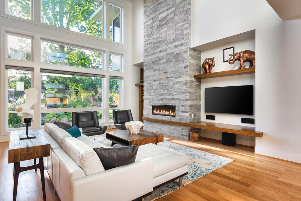 Spacious modish living space featuring a white couch and a pair of black seats along with a fireplace.