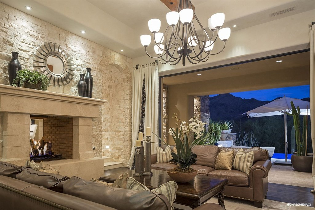 Another rustic and traditional touched interior with soft cream colors neutralized by earthy tones of walnut. Decorative candle holder, chandelier and brick stone fire place give warmth and light, while the wide open entrance allow the fresh air to circulate inside.
