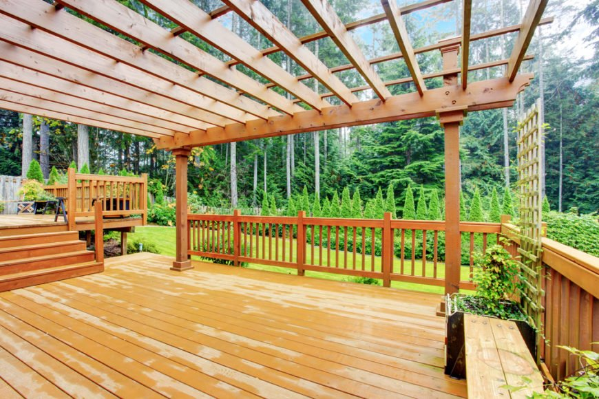 The lower level of this wooden deck is covered by a pergola, which adds style and the slightest bit of shade. Fabric can be looped through to create a canopy, or it can be used like an arbor.
