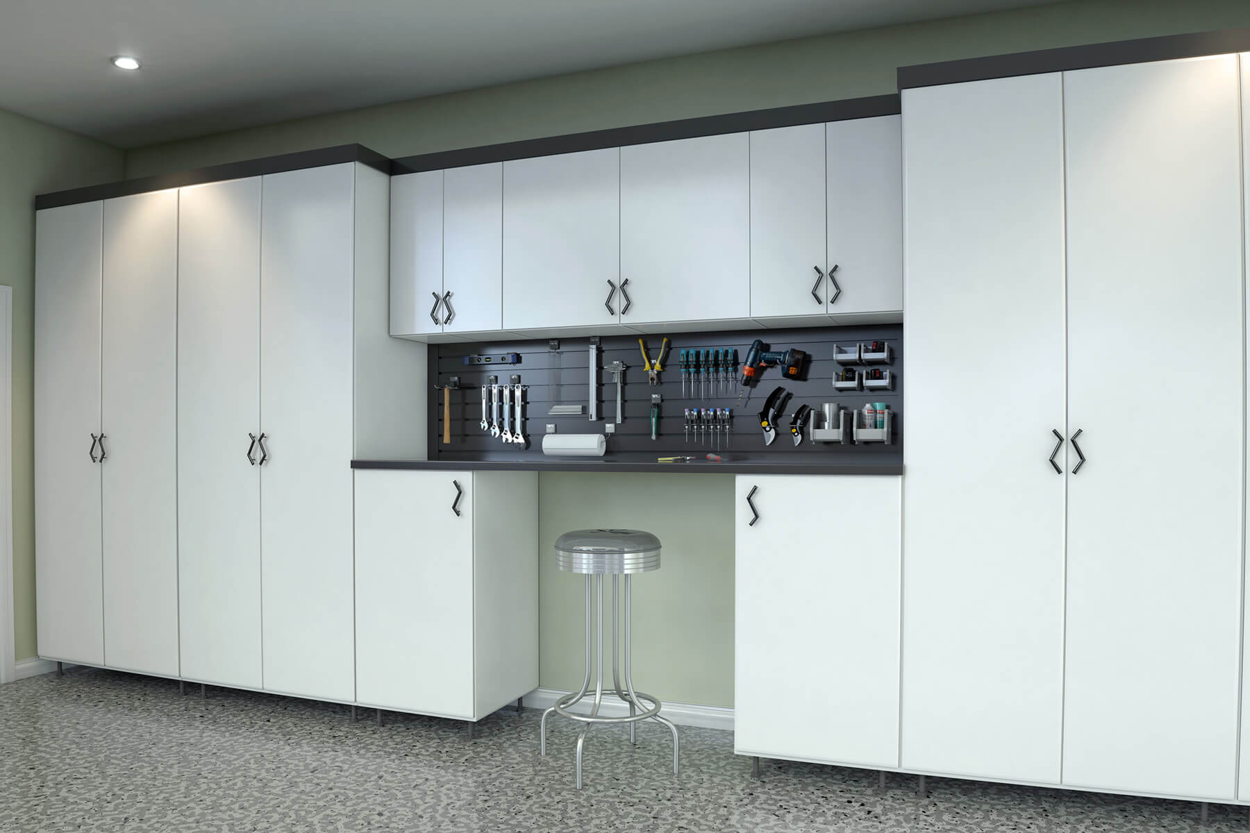 A neat look is achieved in this garage where enclosed white melamine cabinets line up against an entire wall. Featured in the middle is an open tool storage where a workbench stands below.