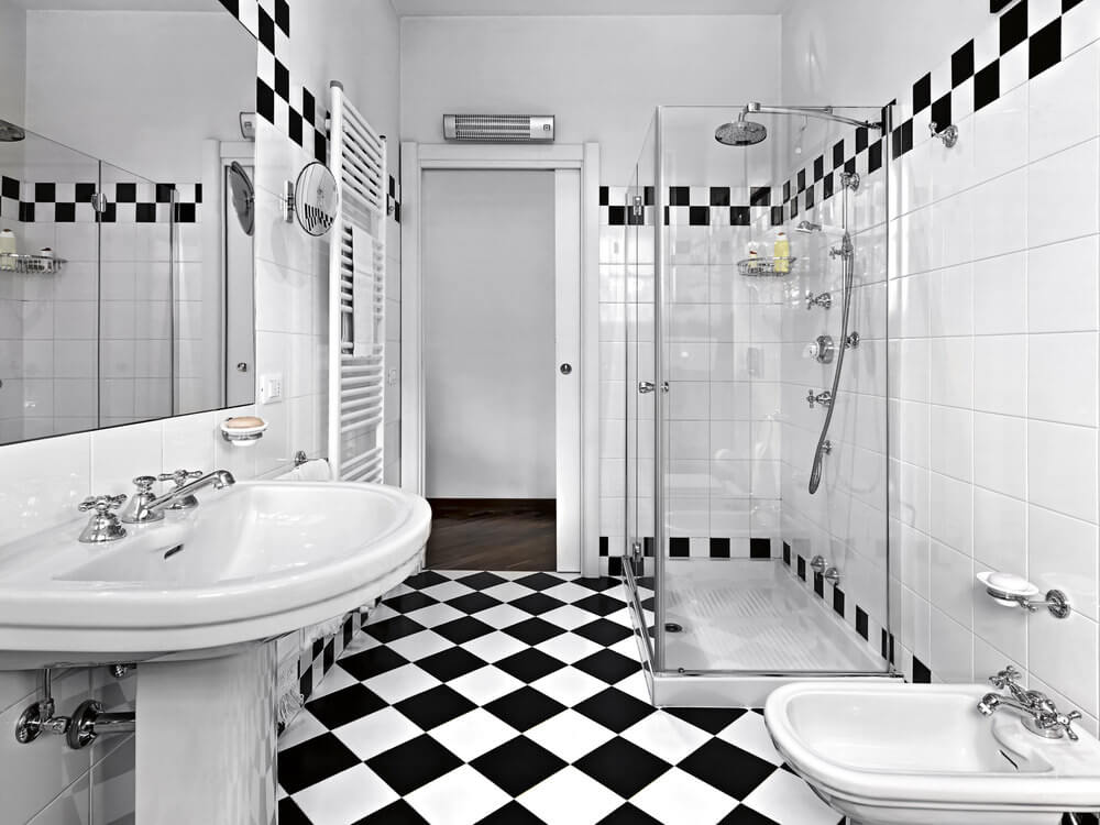 Black and white tile patterns for this bathroom create a rock star color scheme. The ceiling and the sinks are plainly white while the tiled wall is accented with black and white patterns on the upper and lower linings.