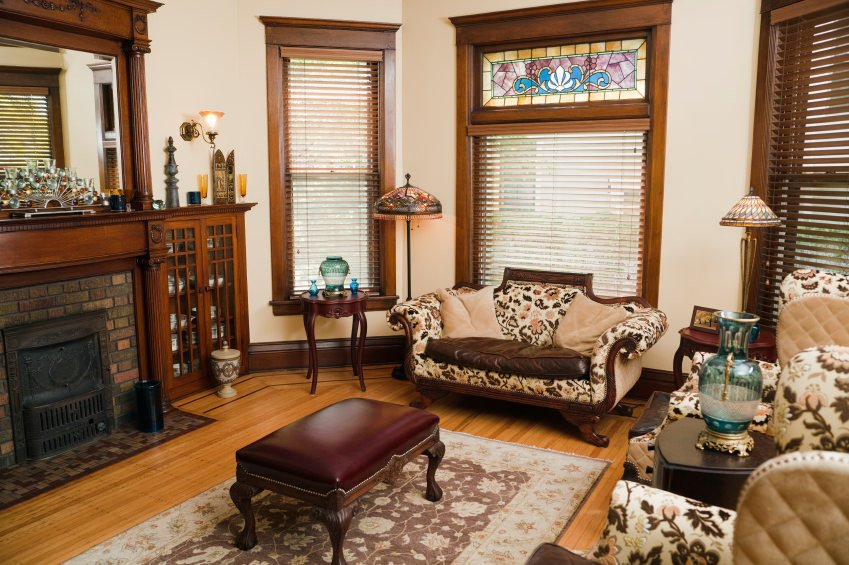 Stained glass, decorative lampshades, vases, floral printed seat cover and parquet flooring with patterned carpet touch this room with a Victorian look.