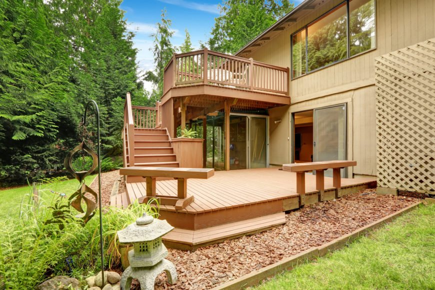 The top level of this deck acts like a balcony and rests above a glass-encased sunroom below.