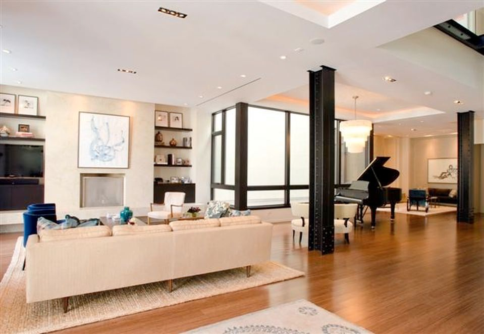 Maple flooring and soft cream wall, sofa and carpet are matching while the dark shades of wall cabinets, metal posts, piano and windows frames give a nice contrast.