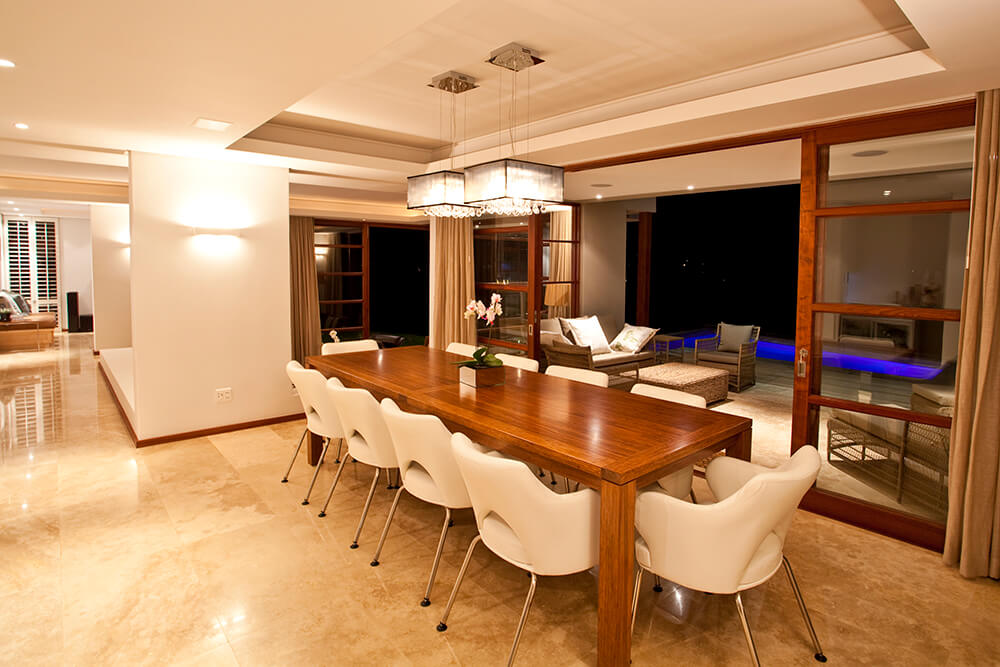 Classy dining area features marble tiled flooring and tray ceiling fitted with lovely chandeliers that hung over a wooden dining table paired with white modern chairs. It has glass sliding doors leading to the patio across a pool.