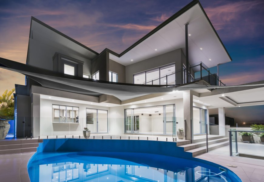This patio has two subtle levels, with a glass balustrade separating the top level from the lower level, which contains the swimming pool. The home also has an incredible balcony on the second floor.