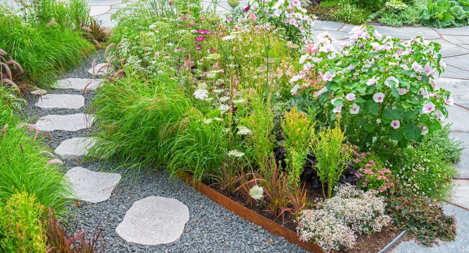 This pathway features gravel and flagstones aligned in a row. Added to this are also bushy ornamental grasses and plants.