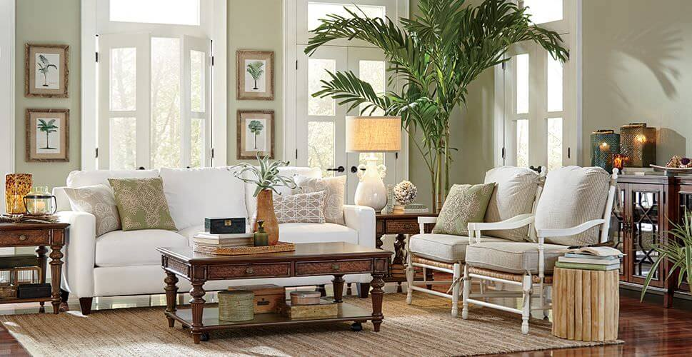 Large living room featuring green walls and white seats. The room has hardwood flooring topped by an area rug.