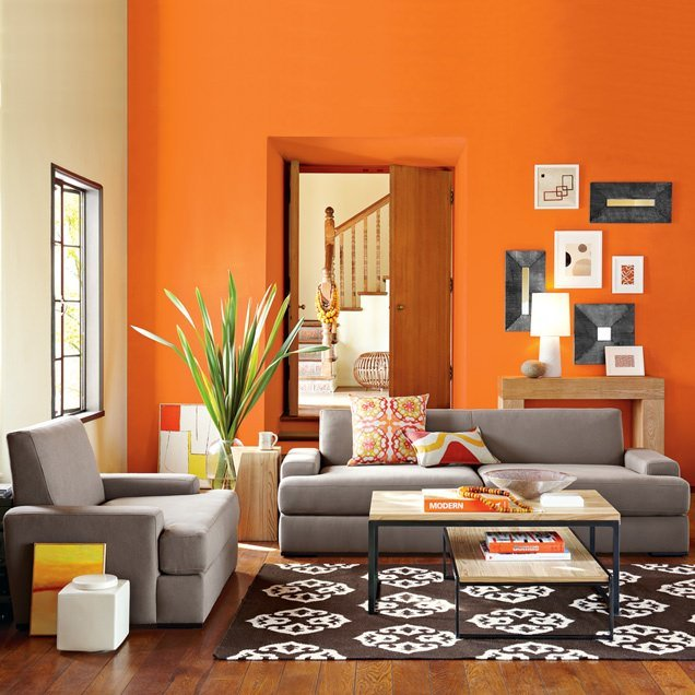 This living room is brightened by both the daylight and the wall painted in bright orange. The paintings leaning on the wall and the armchair also give a bit of orange to the room, as do the large orange art books on the center table and the patterned throw pillows on the sofa set.
