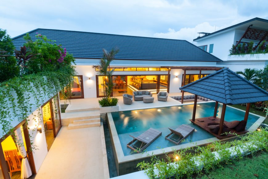 The more subtle levels of this deck and patio disguise the depth of the infinity pool and hot tub. The landscaping is lush and seemingly tropical.