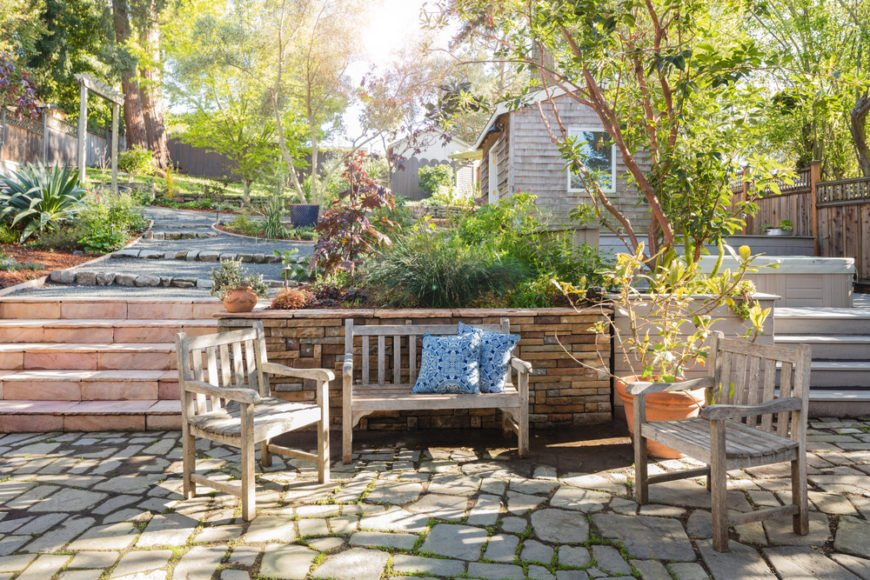 A large planter separates the walkway between the two distinct areas of this stone patio and deck. Hidden just behind the tree is a hot tub, while a more casual sitting area is below, against the planters.