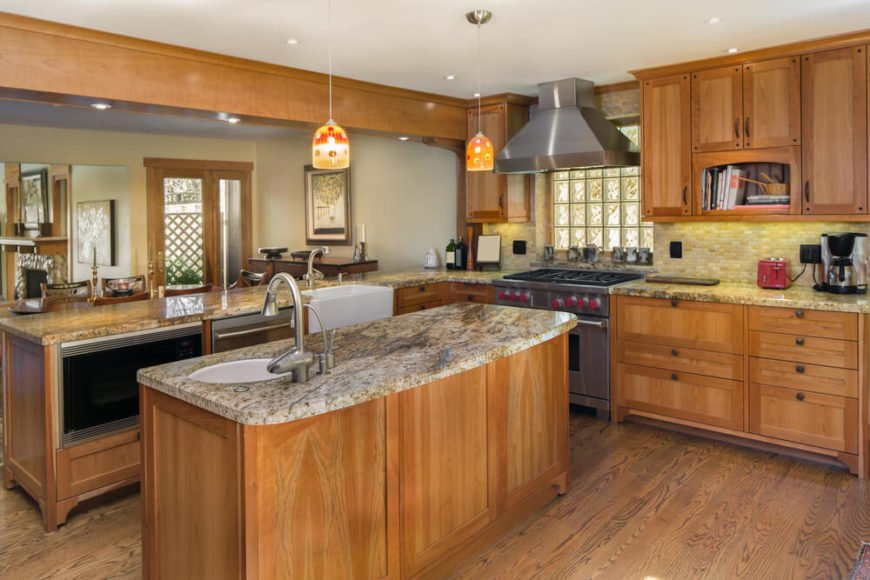 The soft, natural materials and colors of this kitchen are broken by two small Tiffany style pendant lights above the lengthy center island. Oak flooring contrasts and yet meshes perfectly with the lighter grained wood of the cabinets.
