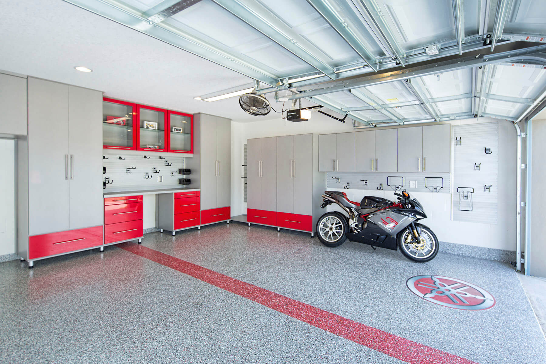 This garage features the combination of red and gray in its melamine cabinets and storage units. The industrial steely gray is easily set off by the bold loud color of red creating a contrasting overall look for the garage.